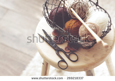 stock-photo-vintage-knitting-needles-scissors-and-yarn-inside-old-wire-basket-on-wooden-stool-still-life-269218337
